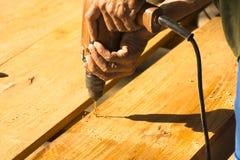 Equipe o carpinteiro que usa a broca elétrica em uma prancha em seu local de trabalho Imagem de Stock