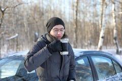 Equipe o chá quente da bebida da caneca exterior no dia de inverno Fotografia de Stock Royalty Free