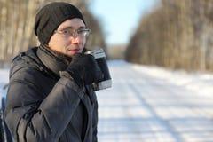 Equipe o chá quente da bebida da caneca exterior no dia de inverno Imagem de Stock Royalty Free