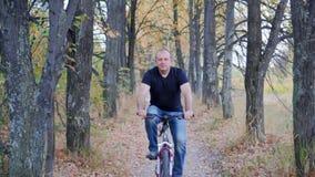 Equipe o ciclista a montar uma bicicleta na floresta do outono vídeos de arquivo