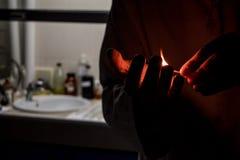 Equipe o cientista que guarda um fósforo iluminado no laboratório Imagem de Stock