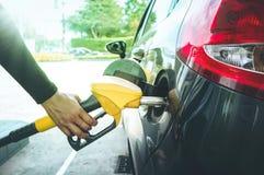 Equipe o combustível de bombeamento da gasolina da mão do ` s no carro no posto de gasolina foto de stock royalty free