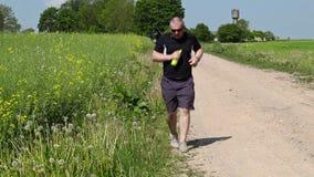 Equipe o corredor ao longo da borda da estrada rural no verão filme