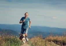 Equipe o corredor com seu cão no planalto da montanha Imagem de Stock Royalty Free