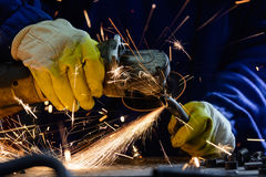 Equipe o corte da tubulação de aço com um moedor de ângulo produzindo faíscas quentes Imagens de Stock Royalty Free