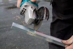 Equipe o corte de uma barra de metal com uma serra circular Foto de Stock Royalty Free
