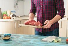 Equipe o cozimento da carne na tabela de madeira na cozinha home Imagem de Stock