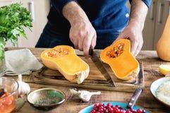 Equipe o cozimento da polpa de butternut na tabela de madeira na cozinha Imagens de Stock