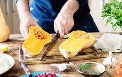 Equipe o cozimento da polpa de butternut na tabela de madeira na cozinha Imagem de Stock