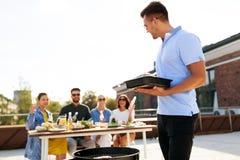 Equipe o cozimento no BBQ e nos amigos no partido do telhado fotografia de stock royalty free