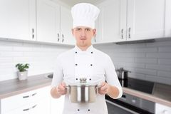 Equipe o cozinheiro chefe no uniforme com a caçarola na cozinha moderna Fotografia de Stock