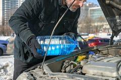 Equipe o enchimento de um tanque da arruela do para-brisa de um carro pelo anticongelante na rua ocupada de Moscou no inverno imagens de stock