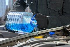 Equipe o enchimento de um tanque da arruela do para-brisa de um carro pelo anticongelante no inverno fora imagens de stock