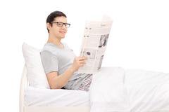 Equipe o encontro na cama e a leitura de um jornal Imagens de Stock