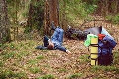 Equipe o encontro na grama perto de sua trouxa em restos de uma pessoa da floresta A após uma viagem longa Modo de vida e recreaç foto de stock royalty free