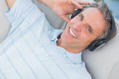 Equipe o encontro no sofá que escuta a música que sorri na câmera Imagem de Stock