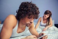 Equipe o encontro usando o smartphone e a mulher que sentam-se na cama imagem de stock royalty free