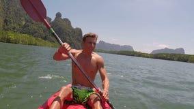 Equipe o enfileiramento que kayaking na câmera bonita pov da ação da lagoa do indivíduo novo que rema no barco do caiaque video estoque