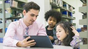 Equipe o estudante do professor e da criança que aprende e que olha na tabuleta devic Imagens de Stock