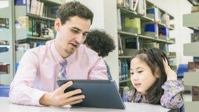Equipe o estudante do professor e da criança que aprende e que olha na tabuleta devic Fotos de Stock