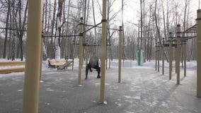 Equipe o exercício do crossfit do treinamento do halterofilista na terra de esportes no parque do inverno filme