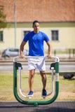 Equipe o exercício em uma máquina em um parque público Foto de Stock