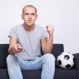 Equipe o fã de futebol que senta-se no sofá com bola e a tevê de observação em casa Imagens de Stock