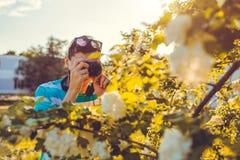 Equipe o fotógrafo que toma imagens das flores no parque no por do sol O indivíduo novo aprecia seu passatempo fora Foto de Stock