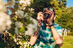 Equipe o fotógrafo que toma imagens das flores no parque no por do sol O indivíduo novo aprecia seu passatempo fora Foto de Stock Royalty Free