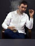 Equipe o fumo de um charuto com um vidro do uísque Imagem de Stock Royalty Free