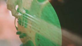 Equipe o guitarrista baixo que joga a guitarra elétrica na fase do concerto vídeos de arquivo