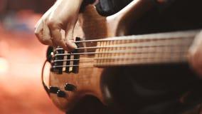 Equipe o guitarrista baixo que joga a guitarra elétrica na fase do concerto video estoque