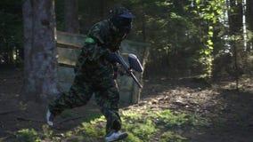 Equipe o jogador no jogo do paintball com a arma que corre na escala de tiro na floresta filme