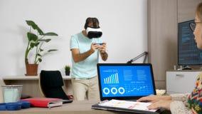Equipe o jogo com auriculares de VR quando sua amiga trabalhar no computador na mesma sala filme