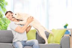 Equipe o jogo com um cachorrinho assentado no sofá em casa Fotografia de Stock Royalty Free