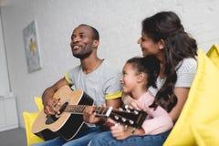 equipe o jogo da guitarra e o canto para a esposa e a filha imagem de stock royalty free