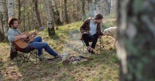 Equipe o jogo da guitarra e da mulher que afagam o cão junto em torno do lugar do fogo Férias exteriores da barraca de acampament vídeos de arquivo