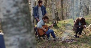 Equipe o jogo da guitarra e da mulher que afagam o cão junto em torno do lugar do fogo Férias exteriores da barraca de acampament filme
