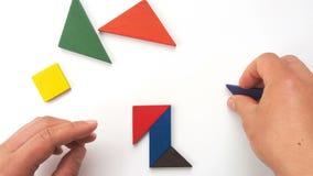 Equipe o jogo do tangram de madeira e dando forma a lhe goste de um pessoa que anda lentamente vídeos de arquivo