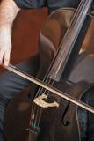 Equipe o jogo do violoncelo, ascendente próximo da mão Instrumento musical da orquestra do violoncelo que joga o músico Foto de Stock Royalty Free