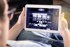 Equipe o jogo em um casino em linha com tabuleta fotografia de stock