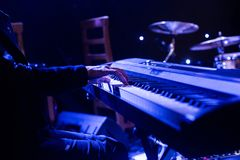 Equipe o jogo no teclado do sintetizador na fase durante o concerto Foto de Stock