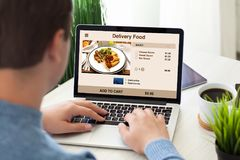 Equipe o laptop com alimento da entrega na tela na sala Foto de Stock Royalty Free