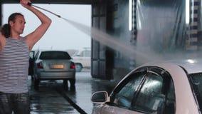 Equipe o lavagem de seu carro com pulverizador de água da arruela de alta pressão Autosserviço da lavagem de carros Homem caucasi vídeos de arquivo