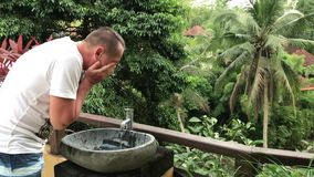 Equipe o lavagem de suas mãos e cara fora com uma vista tropical bonita Conceito do frescor e da ecologia Ilha de Bali filme