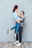 Equipe o levantamento acima de sua amiga no fundo cinzento foto de stock