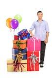 Equipe o levantamento ao lado de uma pilha dos presentes e dos balões Fotografia de Stock