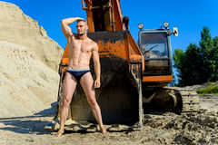 Equipe o levantamento em um maiô em um fundo de uma escavadora Imagens de Stock Royalty Free