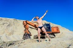 Equipe o levantamento em um maiô em um fundo de uma escavadora Fotos de Stock