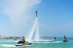 Equipe o levantamento no flyboard novo na praia tropical das caraíbas Emoções humanas positivas, sentimentos, alegria Homens boni fotografia de stock royalty free